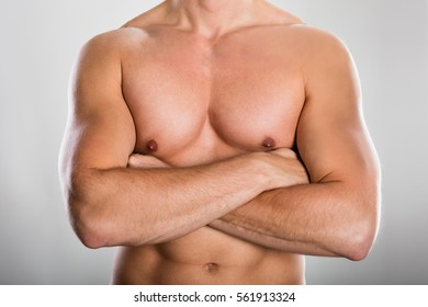 Close-up Of A Shirtless Man With Muscular Build Against Grey Background
