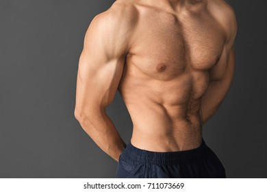 Close-up shirtless man showing muscles of his body.