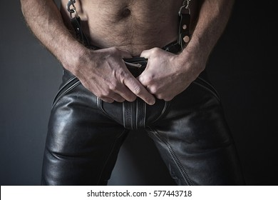 closeup of shirtless man wearing black leather pants