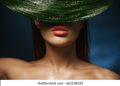 Closeup of shirtless woman with beautiful collarbone hiding behind leaf.