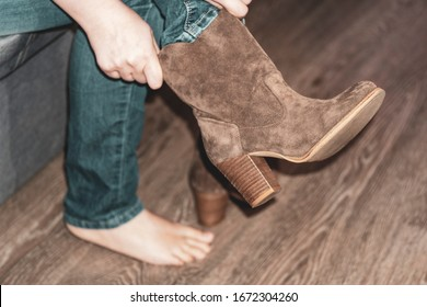 close-up. Shoe fitting. Female hands put on a boot on a leg. The girl puts on footwear. Concept of buying, trying on shoes and boots.