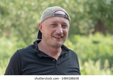 Closeup shoot of caucasian man in a cap. People and lifestyle concept. Portrait of middle aged man in nature, outdoors