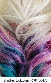 Closeup shoot of female head with fresh dyeing colorful unicorn or rainbow hair.