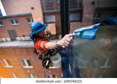 Closeup shoot of industrial rope access abseiler window cleaner wearing full safety harness, helmet fall protection abseiling conducting cleaning window Sydney, high rise building defocused background