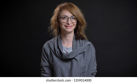 Closeup shoot of middle aged read haired caucasian female in glasses smiling cheerfully while looking forward with background isolated on black