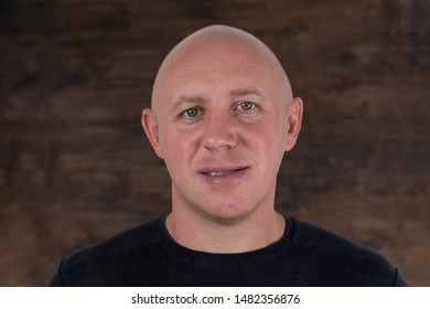 Closeup shoot of middle-aged caucasian bald man looking straight at camera. People and lifestyle concept. Portrait of middle aged man indoors