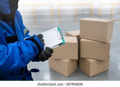 Closeup shooting hand of QC. worker with clipboard checking to goods package boxes in the cold room warehouse., Food cold storage concept