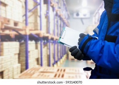 Closeup shooting hand of QC. worker checking goods on delivery in the cold room warehouse., Logistics food and beverage in cold storage concept