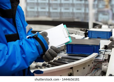 Closeup shooting hand of worker with clipboard checking plastic crate for fruits and vegetables loading on conveyor machine in cold room warehouse, Import and export management system to customer.