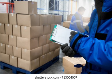 Close-Up shooting hand of worker with clipboard checking goods in freezing room or warehouse. Export-Import Logistics system concept