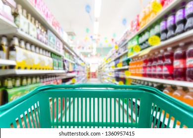 Closeup shopping basket green color with blurred suppermarket background