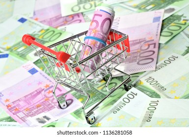 Close-up of shopping cart with roll of banknotes on euro banknotes money - finance purchase concept