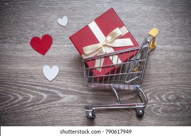 closeup of shopping trolley with gift box concept, love hearts Valentine's Day  on wooden background