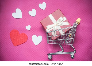 closeup of shopping trolley with gift box concept, love hearts Valentine's Day  on pink background