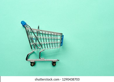 close-up of shopping trolley on turquoise background with some copy space. Flat lay or top view.