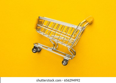 close-up of shopping trolley on yellow background with some copy space