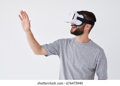Close-up shot of adult bearded man using VR glasses trying to touch objects in virtual reality Isolated white background
