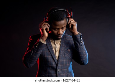 Closeup shot of african american young unshaven man listening music in headphones, looking down, posing in dark. Portrait of stylish DJ with headset, wearing checked suit, isolated on black background