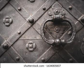A closeup shot of an ancient door in black with metal handle