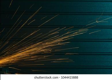 Close-up shot of angle grinder sparks over urban background