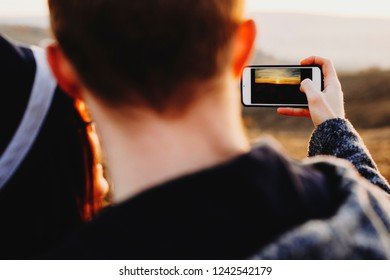 Closeup shot of anonymous couple using smartphone to take picture of amazing sunset in countryside.Crop couple taking photo of sundown