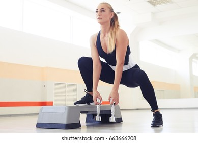 Close-up shot of an athletic woman trainer doing aerobic class with steppers. Sport and health concep. Exercising with hand weights