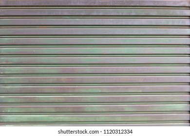A closeup shot of automatic metal roller door used in factory, storage, garage, and industrial warehouse. The corrugated and foldable metal sheet offer space saving and provide urban and rustic feel