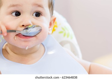 Closeup shot of a baby feeding with the spoon. The small child eats independently