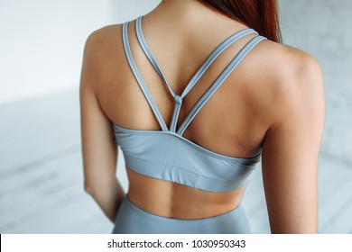 Close-up shot from the back of a female fitness model. Young woman in sportswear with a beautiful body.