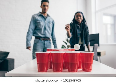 closeup shot of ball flying in plastic cup in beer pong game and young multicultural couple standing behind