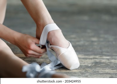 Close-up shot of a ballerina taking off the ballet shoes sitting on the floor in the studio