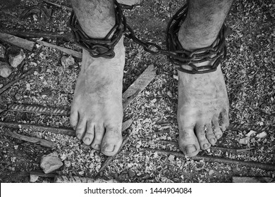 Close-up shot of barefoot men legs tied up with old chain. Crime and murder idea. Black and white