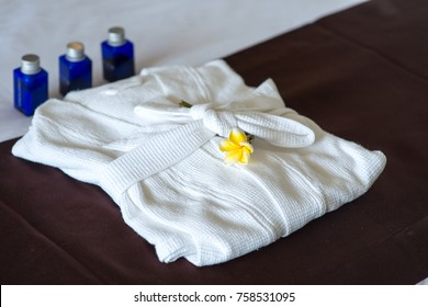 close-up shot of bathroom amenities with bathrobe on bed in hotel room