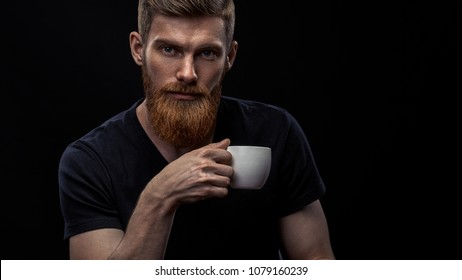 Closeup shot of bearded man drinking coffee and looking at camera Sitting handsome perfect hairstyle man drinking espresso holding cup of coffee in hand Studio shot on black background.