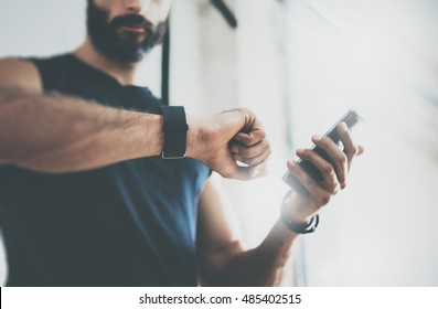 Close-up Shot Bearded Sportive Man After Workout Session Checks Fitness Results Smartphone.Adult Guy Wearing Sport Tracker Wristband Arm.Training hard inside gym.Horizontal bar background.Blurred