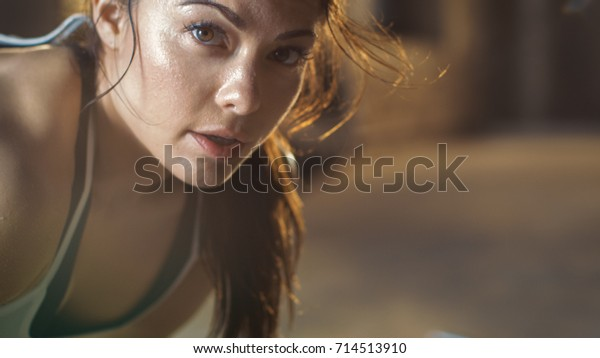 Close-up Shot of a Beautiful Athletic Woman Looks into Camera. She's Tired after Intensive Fitness Exercise.