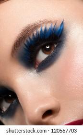 Close-up shot of beautiful female eye with bright fashion makeup. Woman eye with blue false eyelashes