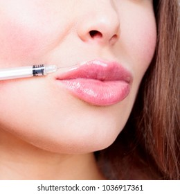 Closeup shot of beautiful female lips and syringe with filler.