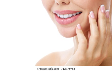Closeup shot of beautiful female smile and manicured fingers, white background.