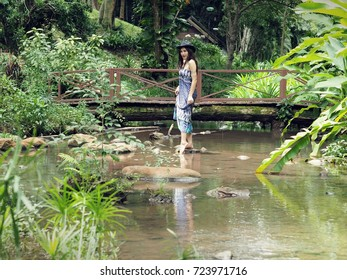 Closeup Shot of A Beautiful Half-Caste Lady in Blue Dress Posing on Stream in A Forest of Mae Hong Son Province, Thailand.  Selective Focus, Blurred Foreground and Background.