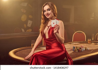 Close-up shot of a beautiful woman posing against a poker table in luxury casino.