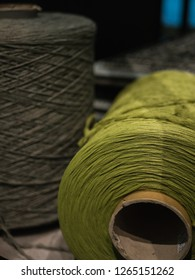 Close-up shot of a big  green thread spool, with grey spool in background