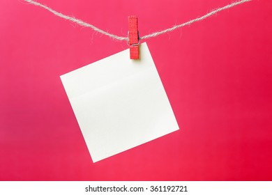 Closeup shot of blank sticky note hanging on line.