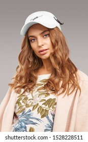 """Close-up shot of blonde European lady with wavy hair in a white top with floral print, pale pink jacket and white baseball cap with an embroidered lettering """"Cablette"""" and decorated with a cable tie."""
