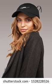 """Close-up shot of blonde European lady with wavy hair in a white top with floral print, gray jacket and a black baseball cap with an embroidered lettering """"Cablette"""" and decorated with a cable tie."""