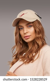 """Close-up shot of blonde European lady with wavy hair in a white top with floral print, pale pink jacket and beige baseball cap with an embroidered lettering """"Cablette"""" and decorated with a cable tie."""