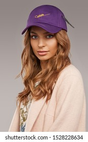 """Close-up shot of blonde European lady with wavy hair in a white top with floral print, pale pink jacket and purple baseball cap with an embroidered lettering """"Cablette"""" and decorated with a cable tie."""