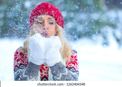 Closeup shot of blonde woman who blows snowflakes from her hands in the winter forest