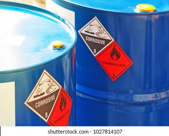 the close-up shot of blue color hazardous dangerous chemical barrels ,have warning labels of corrosive & flammable liquid in daylight on daytime.
