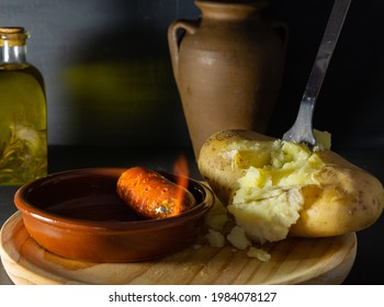 A closeup shot of boiled potatoes with flambe sausage on a wooden tray